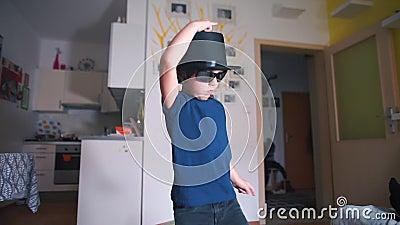 Ett barn i glasögon och en hatt dansar arkivfilmer