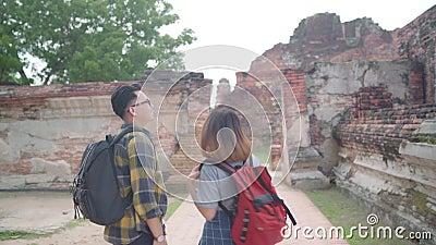 Ett fint par med ryggsäck njuter av sin resa på en fantastisk landmark i traditionell stad lager videofilmer