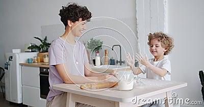 Ett lekfullt barn som klappar händer smutsig med skratt och skrattar åt matlagning med mamma lager videofilmer
