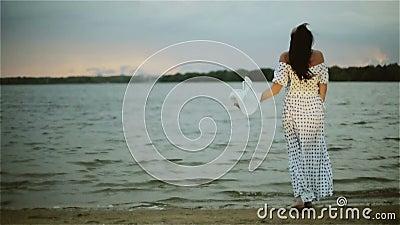 Ett mellersta åldrigt kvinnaanseende på vattenkanten och sätta av hennes stora vita hatt lager videofilmer