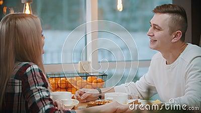 Ett par i kaféet som äter lunch och pratar med varandra samtidigt som de håller hand stock video