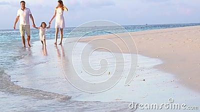Ett par med ett småbarn som går en strand långsam rörelse lager videofilmer