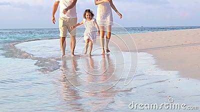 Ett par med ett småbarn som går en strand långsam rörelse arkivfilmer