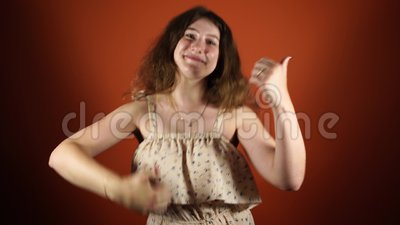 Eu amo-o mulher que faz como um gosto com polegares acima em um fundo alaranjado filme