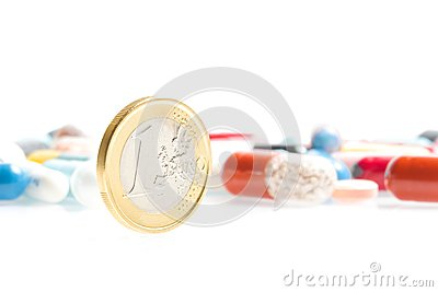 Euro coin in front of medical pills