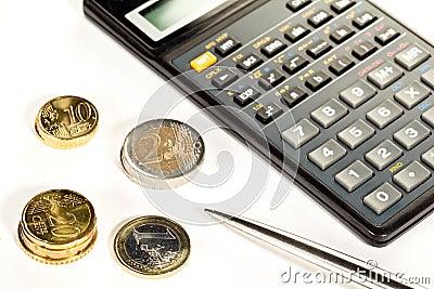 Euro coins, calculator and a pen