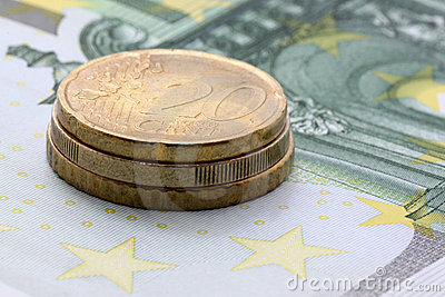 Euro coins on one hundred euro banknote