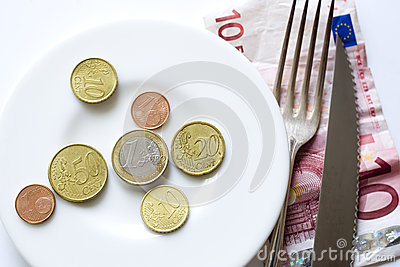 Euro coins on plate fork, knife
