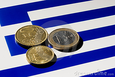 Euro coins on top of the Greek  flag