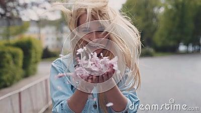 Europejskiej młodej blondynki atrakcyjna dziewczyna rusza się w dół parka, then obraca płatki wiśni okwitnięcie i rzuca zbiory wideo