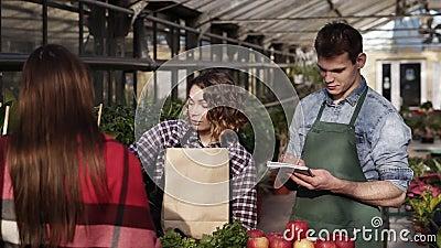 Europese winkelier met een apron geeft biologisch voedsel aan klanten in de kas Vrouw verpakt groenen, vruchten en stock footage