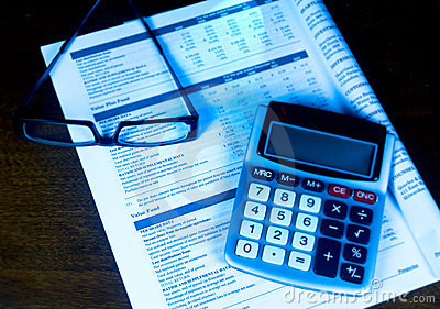 Evaluating a 401k with calculator and eyeglasses.