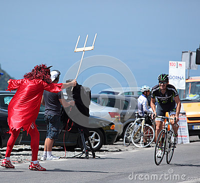 Evil mascot waiting for the cyclist Editorial Stock Photo