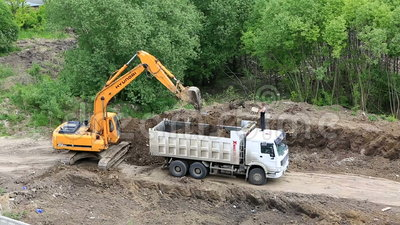 Excavator digging a trench and ground loads trucks stock for Digging ground dream meaning