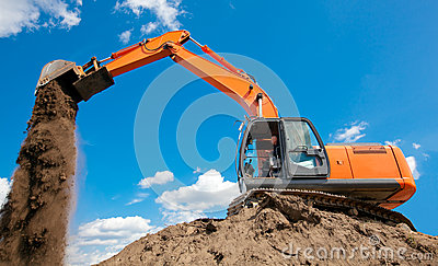 Excavator with metal tracks unloading soil at construction site