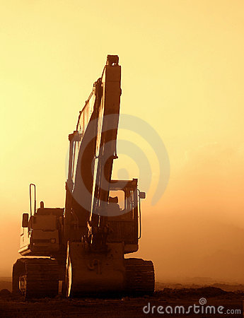 Excavator at Sunset on a Dusty Construction Site