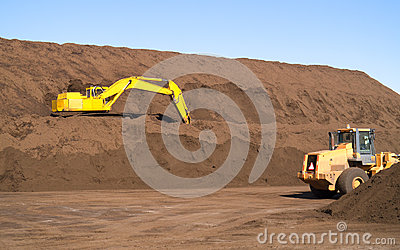 Excavator on Top Soil hill