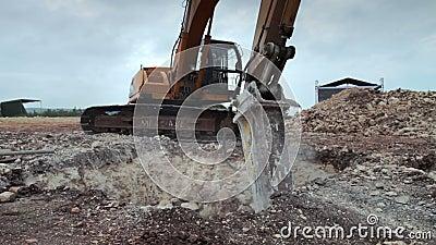 Excavatrice avec le foret de marteau hydraulique au travail décomposant la terre pour la construction banque de vidéos