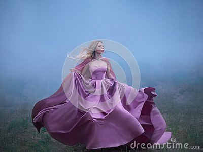 Excellent mysterious blonde lady runs away from a nightmare, a forest monster, her light long expensive royal dress Stock Photo