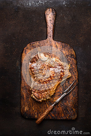Free Excellent Roasted Or Grilled T-bone Steak With Meat Fork On Aged Wooden Cutting Board On Dark Rust Metal Background Royalty Free Stock Photos - 72057378