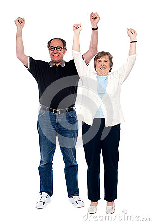 Excited aged couple posing with raised arms