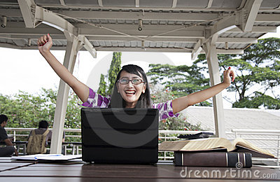 Excited asian woman with laptop and books