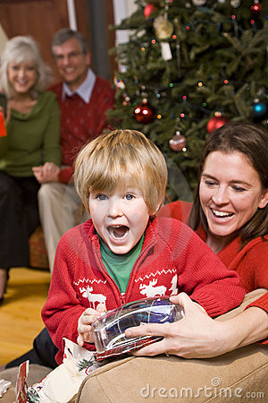 Excited boy with family and presents at Christmas