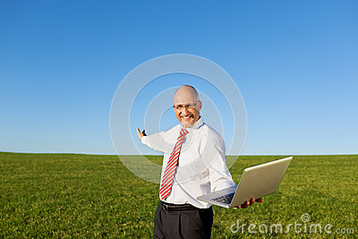 Excited Businessman With Arms Outstretched Holding Laptop On Fil