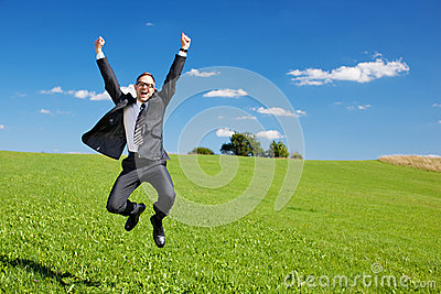 Excited businessman jumps high in the air