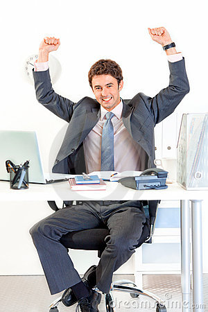 Excited businessman in office rejoicing success