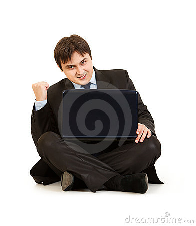 Excited businessman sitting on floor with laptop