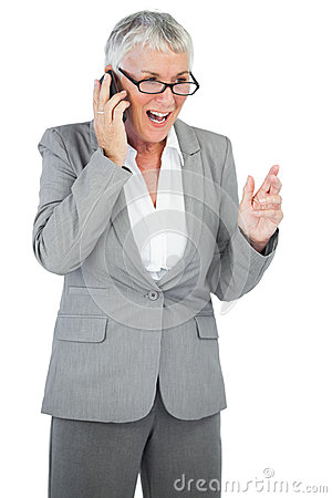 Excited businesswoman calling someone with her mobile phone