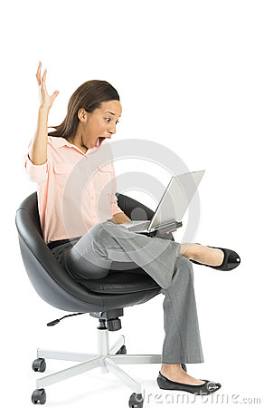 Excited Businesswoman Looking At Laptop While Sitting On Chair