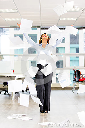 Excited businesswoman throwing papers