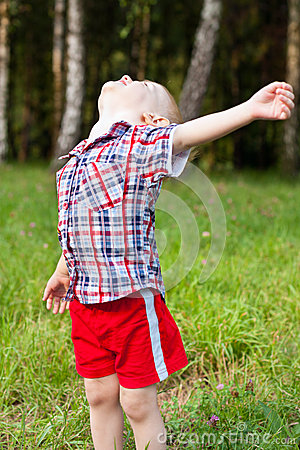Excited child playing outdoor raised his head up