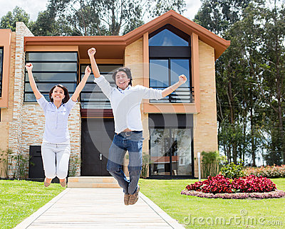 Excited couple about their house