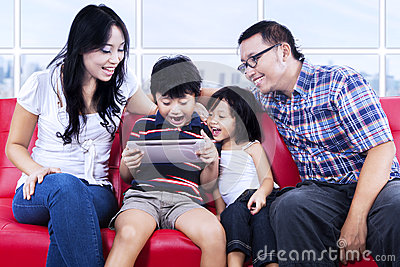 Excited family playing game at apartment
