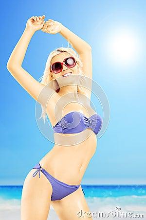 Excited female in bikini enjoying on a beach