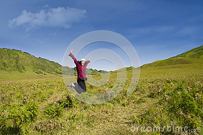 Excited female jumping in grass field