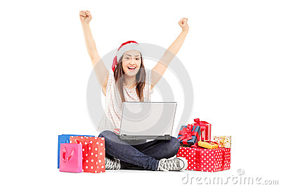 Excited female with santa hat working on laptop and gifts around