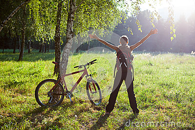 Excited girl cyclist standing in sunny park