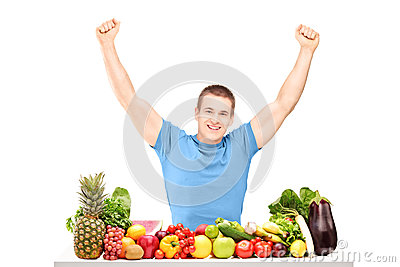 Excited guy gesturing happiness seated on a table full of fruits