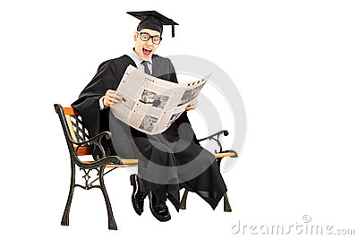 Excited guy in graduation gown reading a newspaper seated on ben