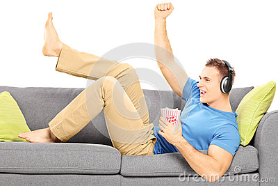 Excited guy lying on a modern couch and listening music