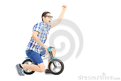 Excited guy riding a small bicycle and gesturing happiness