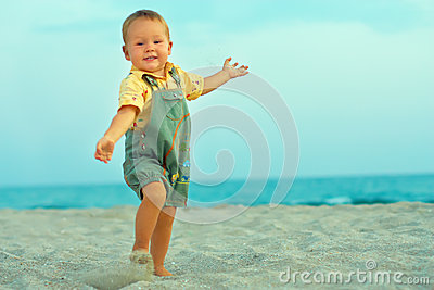 Excited happy baby boy playing on beach