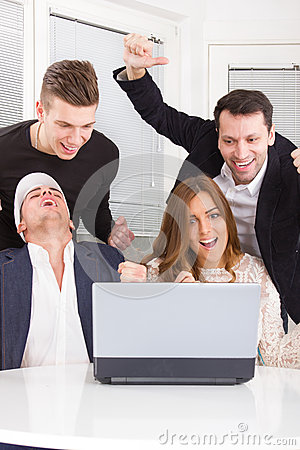 Excited happy group of friends winning online using laptop