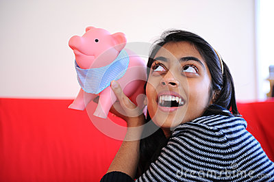 Excited Indian girl holding piggybank
