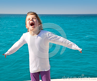 Excited kid girl sailing in a boat open arms