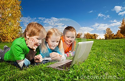 Excited kids with laptop in park